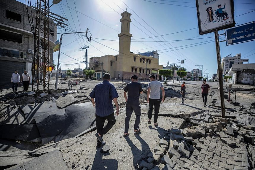 Palestinians are seen inspecting a damaged street following an Israeli air strike in Gaza City on May 13, 2021.