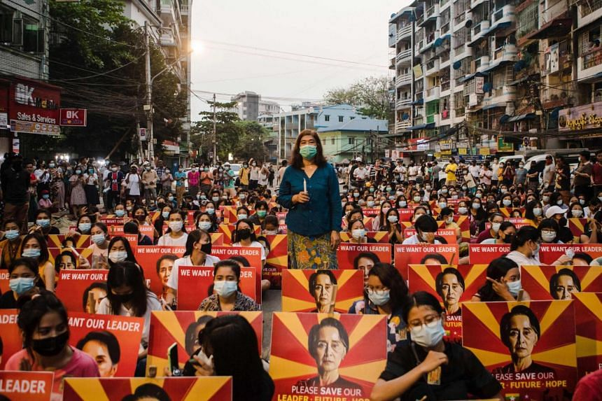 In this photo taken on March 12, 2021, protesters sit along a street before holding a candlelight vigil during a demonstration against the military coup in Yangon.