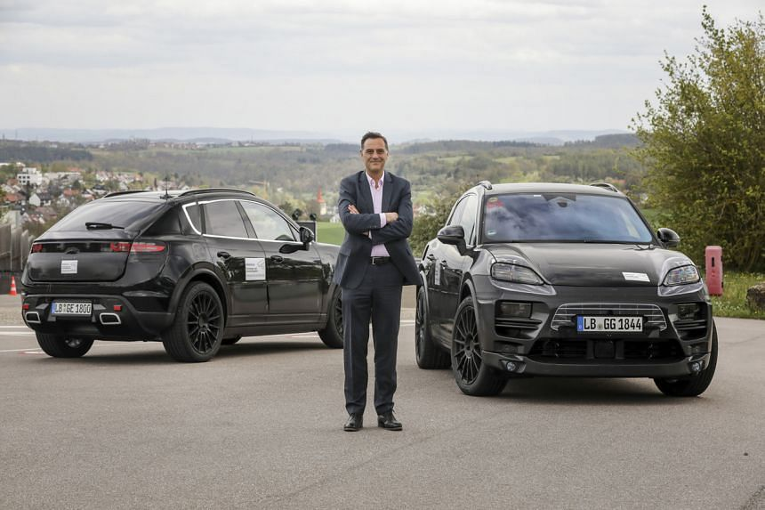 Michael Steiner, Member of the Executive Board, Research and Development, at Porsche Ag, in front of two camouflaged prototypes of the all-electric Macan.