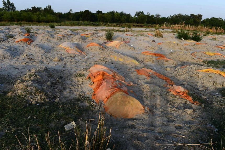 Bodies of suspected Covid-19 victims are seen partially buried in the sand near a cremation ground on the banks of Ganges River in Unnao, India, on May 13, 2021.