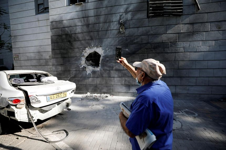 An Israeli man takes a photo with his mobile phone at a residential building after a rocket launched overnight from the Gaza Strip hit it in Ashkelon, Israel, on May 14, 2021.