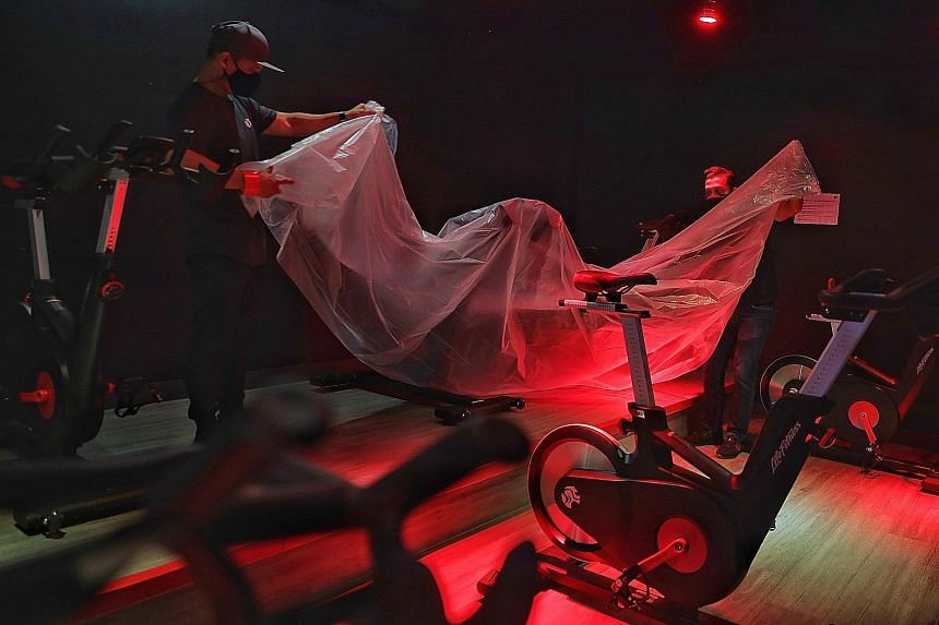 Staff covering up stationary bicycles at a True Fitness gym on May 7, the last day before the reintroduction of phase two measures. Under new guidelines, indoor facilities can offer only low-intensity activities.