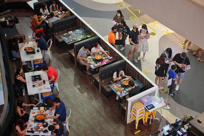Diners at a restaurant at Bugis+ mall yesterday. For many restaurants, clearing the stocks of food in their kitchen was among the first things on their mind.