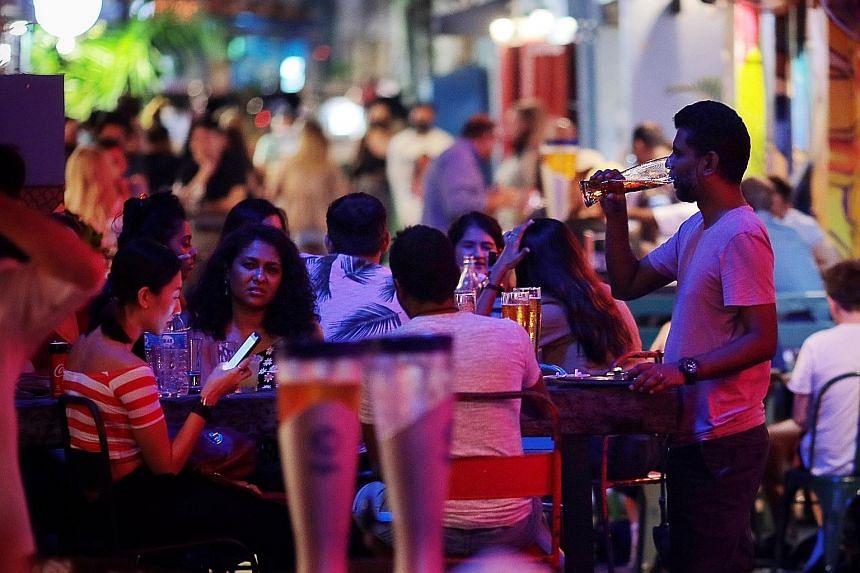 Revellers in Haji Lane yesterday. Starting from today until June 13, gatherings are capped at two people and dining in is prohibited. Hawker stall operators said the tightened measures would cause a slump in business, but those who are tenants of gov
