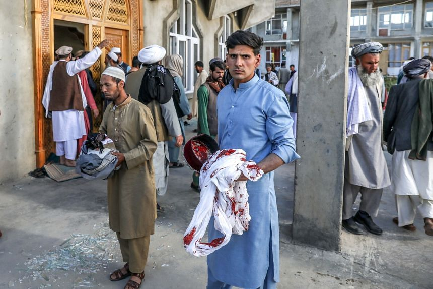 Afghan men hold the belongings of worshippers at the scene of an attack that targeted a mosque in the outskirts of Kabul, on May 14, 2021.