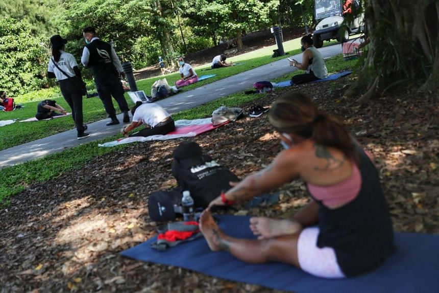 A group attending a yoga session under the eye of NParks officers at the Botanic Gardens on May 16, 2021.