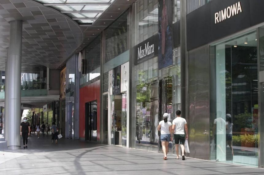 A couple walking along Orchard Road on May 16, 2021.