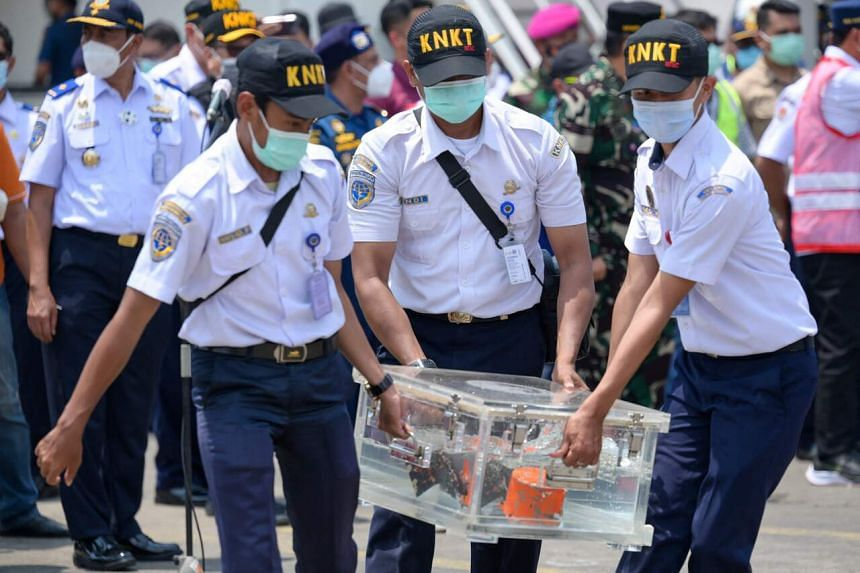 Indonesian officials carry a box containing the Sriwijaya Air Boeing 737-500 passenger jet's blackbox at the port in Tanjung Priok in Jakarta, on March 31, 2021.