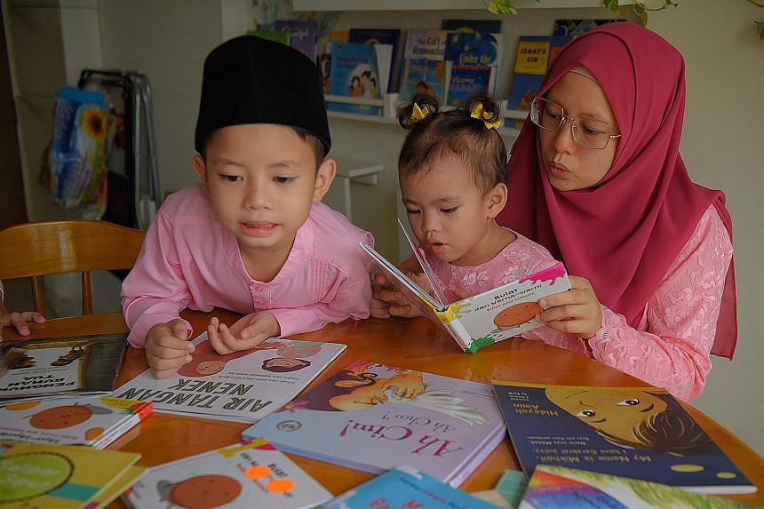 Ms Irene Chia and her sons Yiyang (far left) and Ruikai (left) reading Chinese books at home. Ms Far'ain Jaafar reading Malay books with her son Khalief Syafiq and daughter Nuhyah Syafiq to build the children's fluency in their mother tongue.