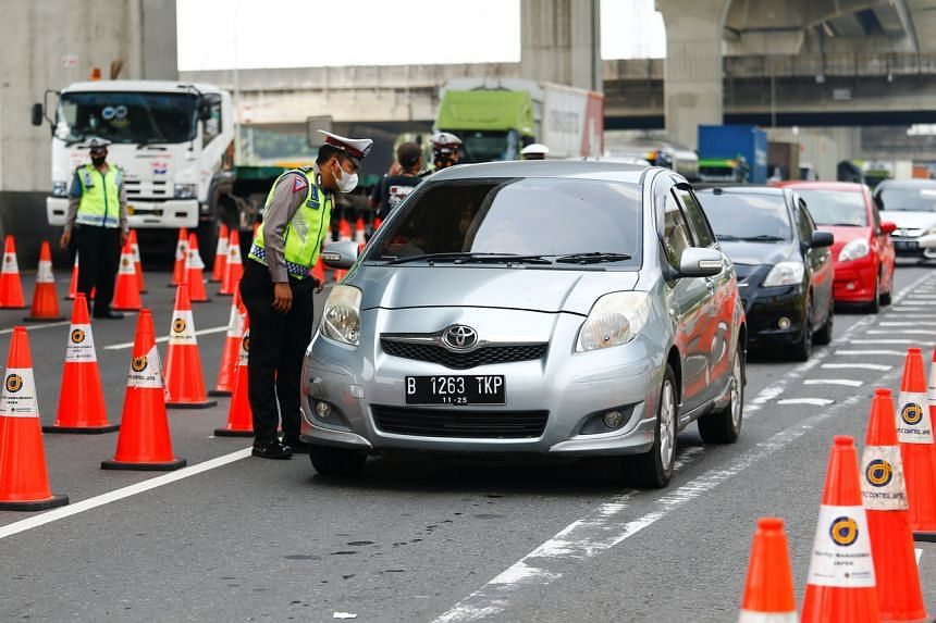 A police officer inspects a car at a checkpoint in Cikarang, Bekasi, on the outskirts of Jakarta, on May 17, 2021.