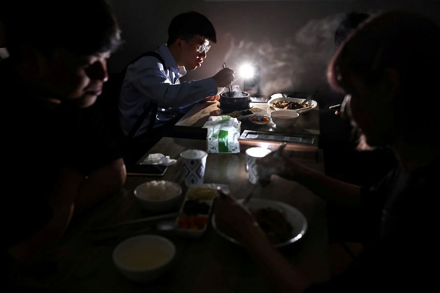 People using the light from their phone while experiencing a blackout in Taipei on May 13, 2021.