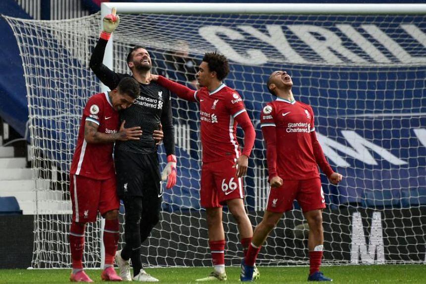 Liverpool's Brazilian goalkeeper Alisson Becker (second from left) celebrates scoring his team's second goal.