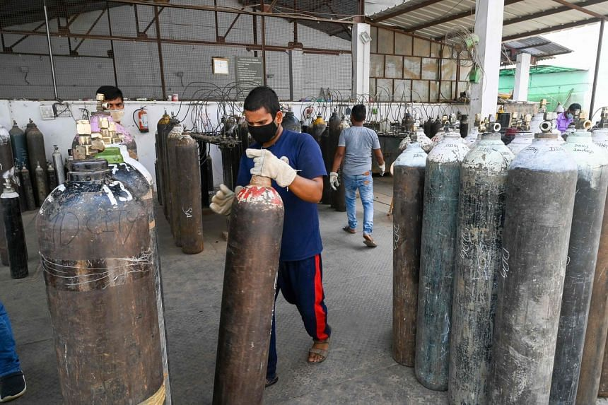 A man moves a medical oxygen cylinder to be loaded in an army truck bound for a care centre in New Delhi on May 12, 2021.