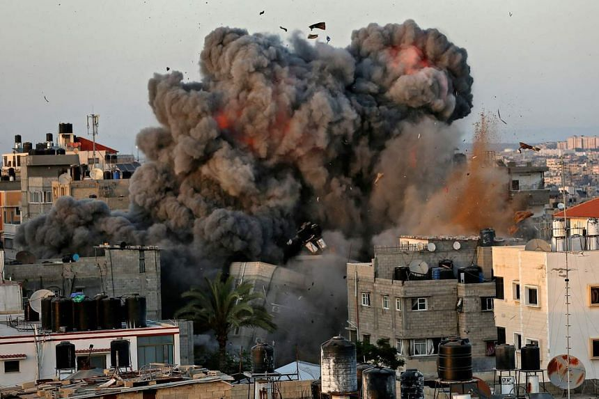 Smoke erupts from a building in Gaza City during an Israeli air strike on May 16, 2021.
