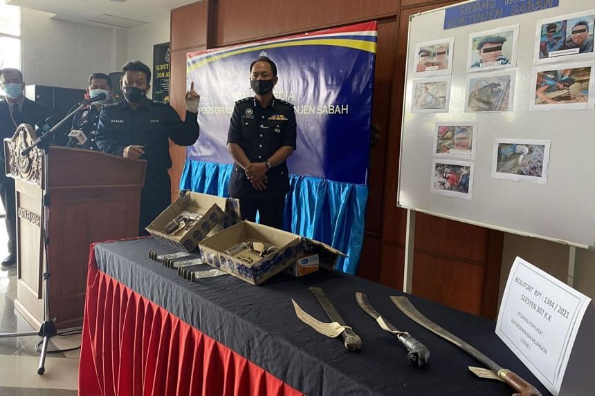 Sabah police commissioner Hazani Ghazali (third from left) with seized weapons and photos of the suspects.