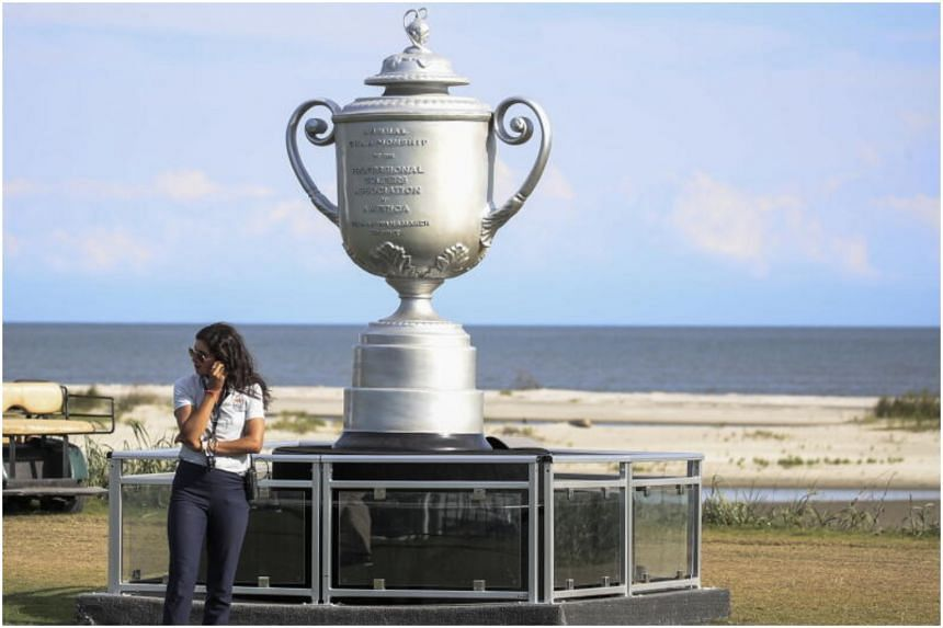 A woman stands next to a large replica of the PGA Championship Wanamaker Trophy on the Ocean Course at Kiawah Island, South Carolina, on May 17, 2021.