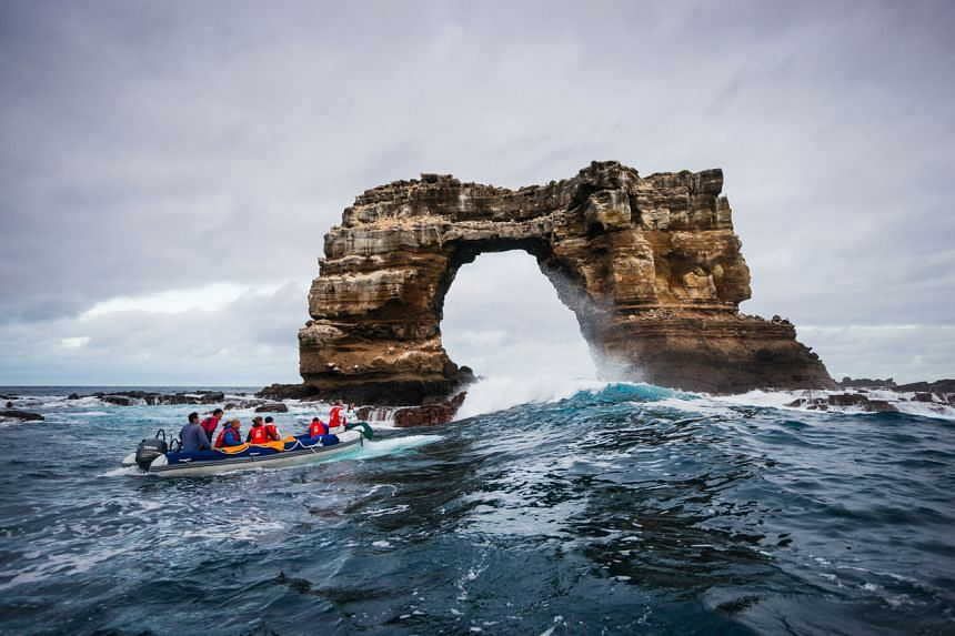 In a photo from Oct 1, 2012, tourists admire Darwin's Arch off the Galapagos Islands.