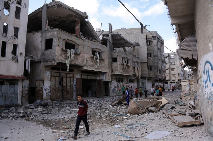 People inspect damaged buildings in Gaza City, on May 17, 2021.
