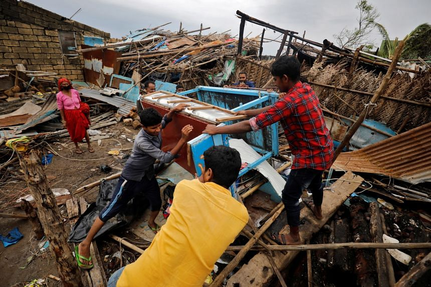 People salvage their belongings from a damaged house after Cyclone Tauktae hit Navabandar village, in Gujarat, on May 18, 2021.