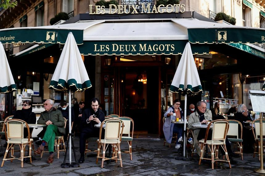 Customers sit on the terrace of the cafe and restaurant Les Deux Magots in Paris on May 19, 2021.