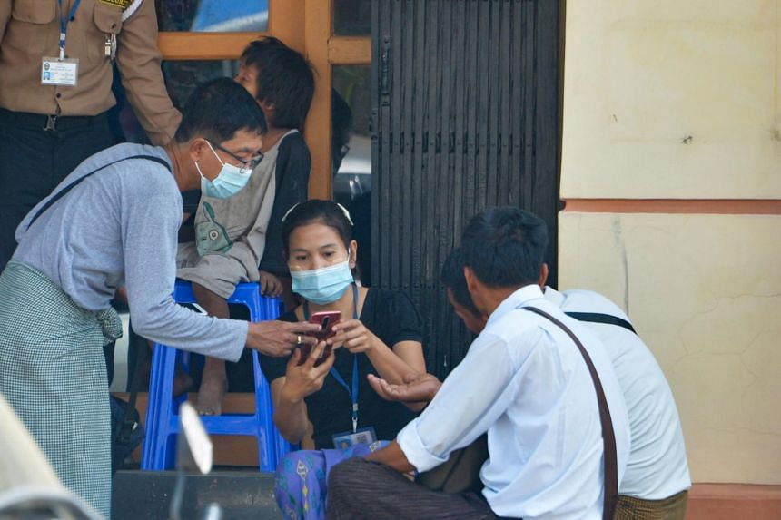 People use their mobile phones to check the connection and Facebook outside an Internet shop in Naypyidaw on March 16, 2021.