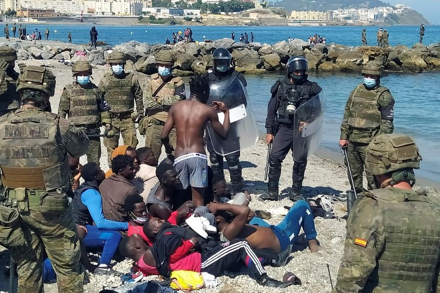 Spanish soldiers talk to migrants after crossing over to Ceuta, Spanish enclave on the north of Africa on May 18, 2021.