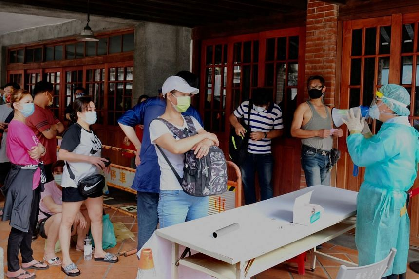 A healthcare worker speaks to local residents who queued up for Covid-19 testing at Wanhua District in Taipei, on May 19, 2021.