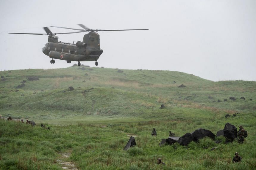 A Chinook helicopter flies over a field during a joint military drill between Japan Self-Defense Forces, French Army and US Marines, on May 15, 2021.