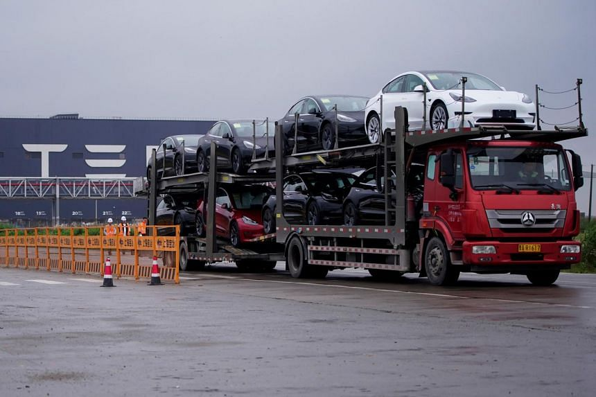 A truck transports new Tesla cars at its factory in Shanghai on May 13, 2021.