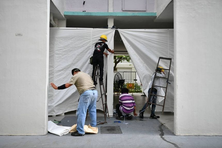 Workers putting up tarps over the barricades at Block 506 Hougang Avenue 8 on May 21, 2021.