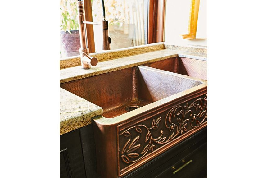 A carved copper kitchen sink custom-made in India.