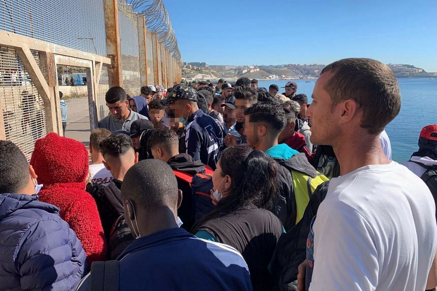 A group of people try to cross the border fence separating Morocco from Spain's Ceuta territory on May 19, 2021.