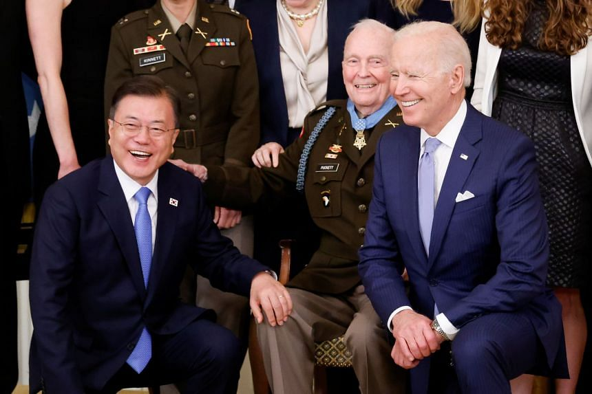 South Korean President Moon Jae-in (left) and US President Joe Biden (right) pose for a picture with Korean War-era Army Colonel Ralph Puckett at the White House in Washington.