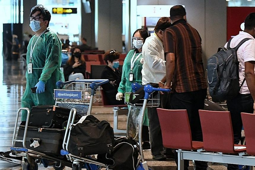 Masked passengers at the arrival hall of Changi Airport Terminal 1 on April 30. As the more transmissible Covid-19 variants appear able to spread in enclosed spaces despite existing infection prevention and control protocols, these measures may need