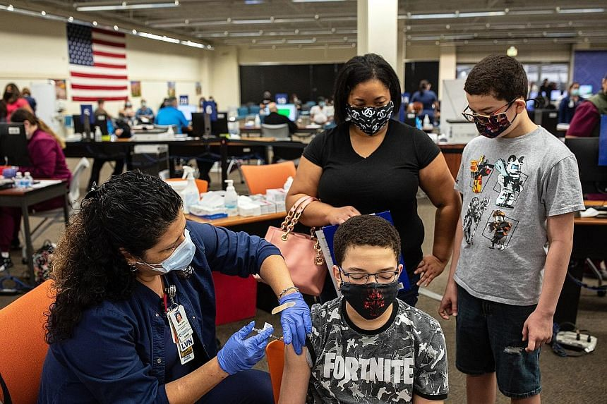 A 13-year-old boy getting a Pfizer-BioNTech jab at a mall in Texas on May 13. In Singapore, the Expert Committee on Covid-19 Vaccination said it had recommended the Pfizer vaccine for those aged 12 to 15 years following HSA's approval, and urged all