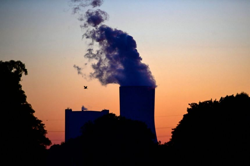 Steam rises from the cooling tower of a coal-fired power plant in western Germany.