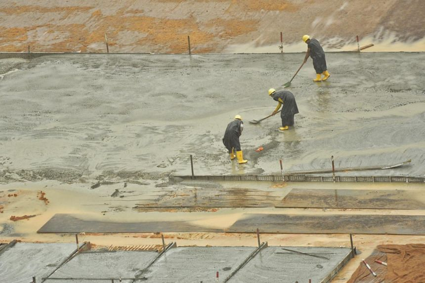Migrant workers at work, amid heavy rain, at the Housing Board construction site of Dakota One.