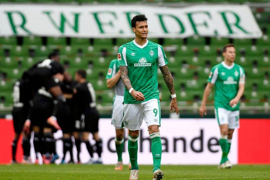 Werder Bremen's Davie Selke looks dejected as Borussia Moenchengladbach's Marcus Thuram celebrates scoring their second goal with teammates.