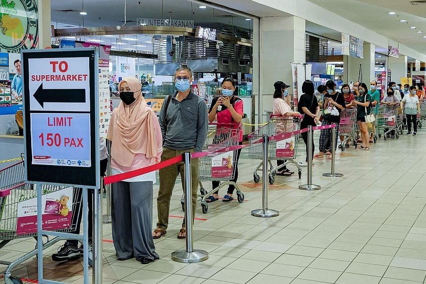 People lining up to buy essentials at a supermarket on Friday. There were long queues at stores ahead of the government announcement on stricter movement curbs yesterday.