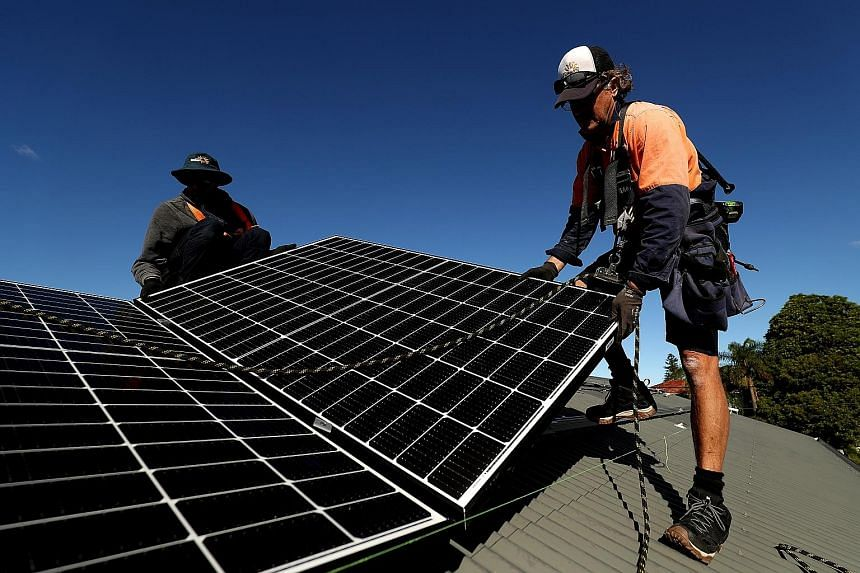 Workers installing solar panels on the rooftop of a residential property in Sydney last Monday. Australia's home solar power uptake is among the highest in the world, and if more households also install batteries to store the solar power, it would gr