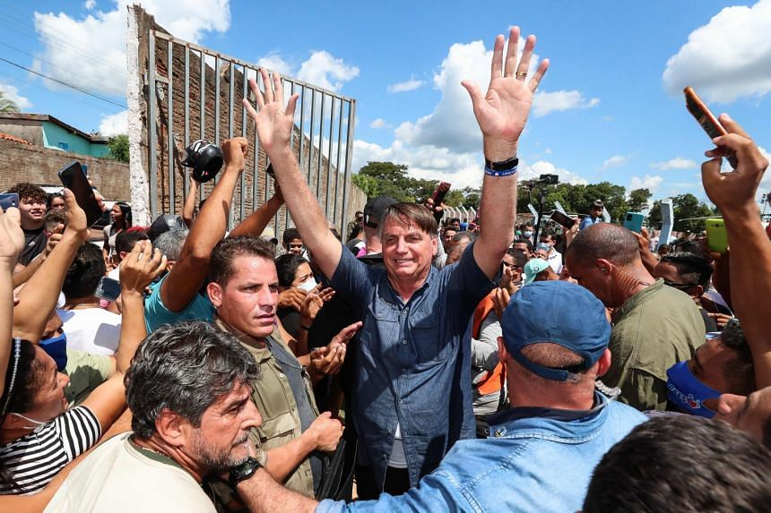 Bolsonaro greets a crowd during a non-scheduled visit to the city of Senador La Rocque, in Maranhao state, on May 21, 2021.