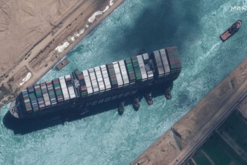 A satellite image shows the MV Ever Given container ship and tugboats in the Suez Canal on March 29, 2021.
