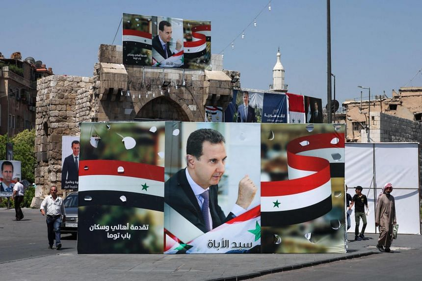 People walk next to election campaign billboards depicting Syrian President Bashar al-Assad, in Damascus on May 23, 2021.