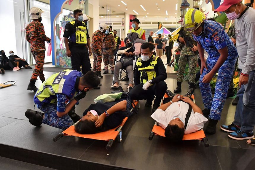 Emergency service staff tending to victims of the LRT crash in Kampung Baru station, on Monday.