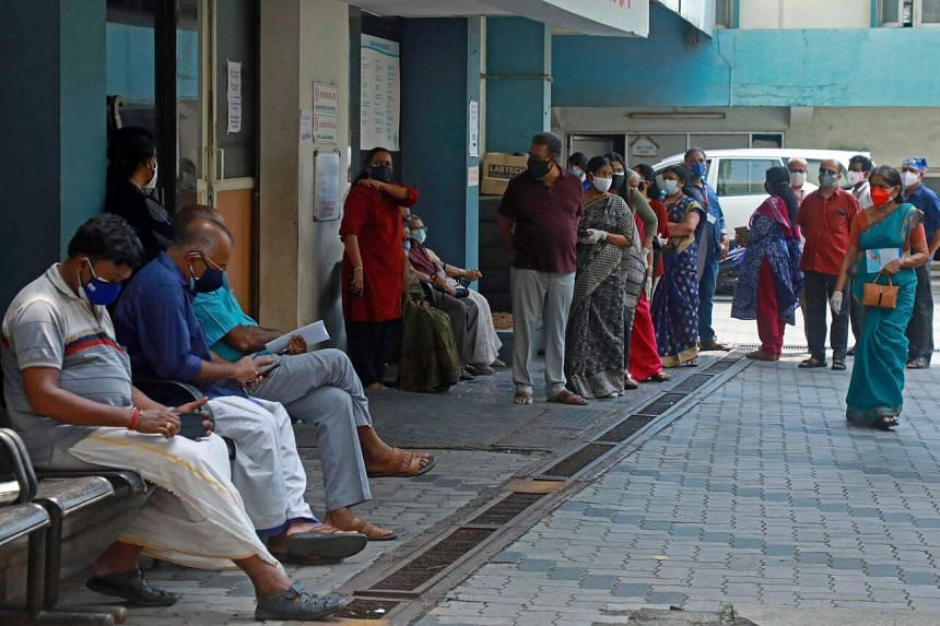 People wait for their turn to get a dose of the Covid-19 vaccine at a treatment centre in Kochi on May 7, 2021.