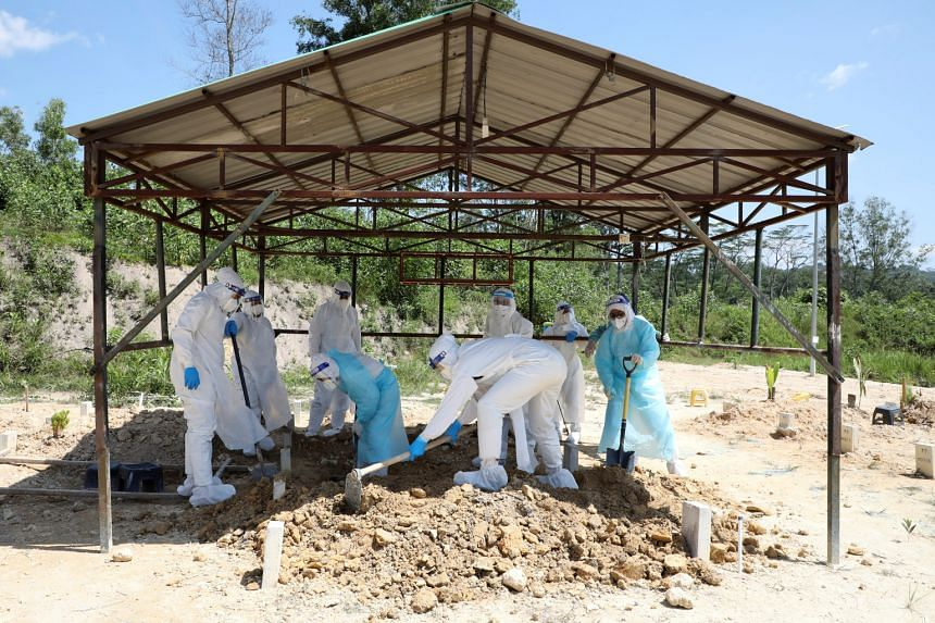 People in protective suits taking part in the burial of a Covid-19 victim at a cemetery in Gombak, Selangor, on Sunday.