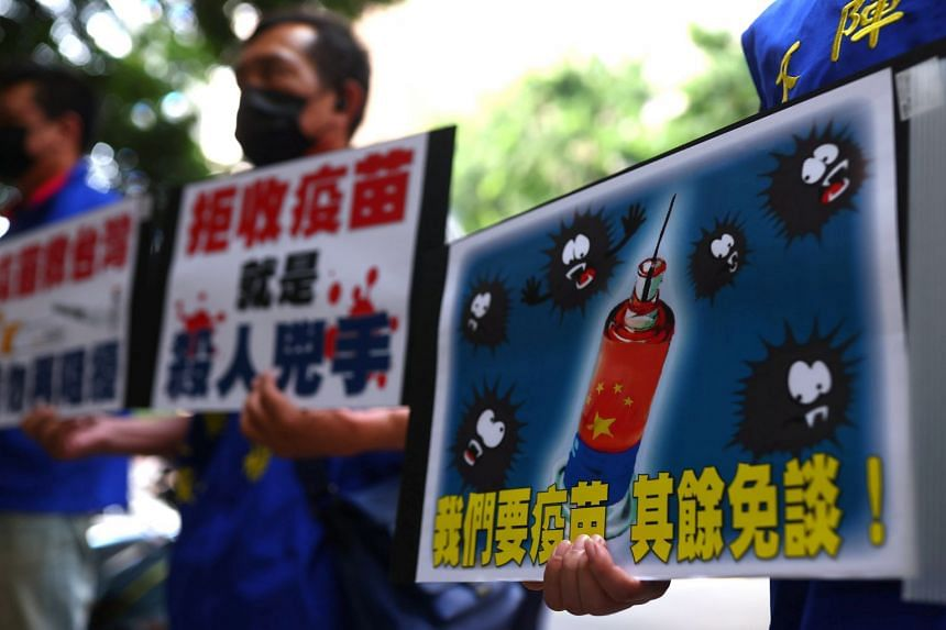 People hold placards calling for the Taiwan government to allow the use of Covid-19 vaccines from China, in Taipei, on May 24, 2021.