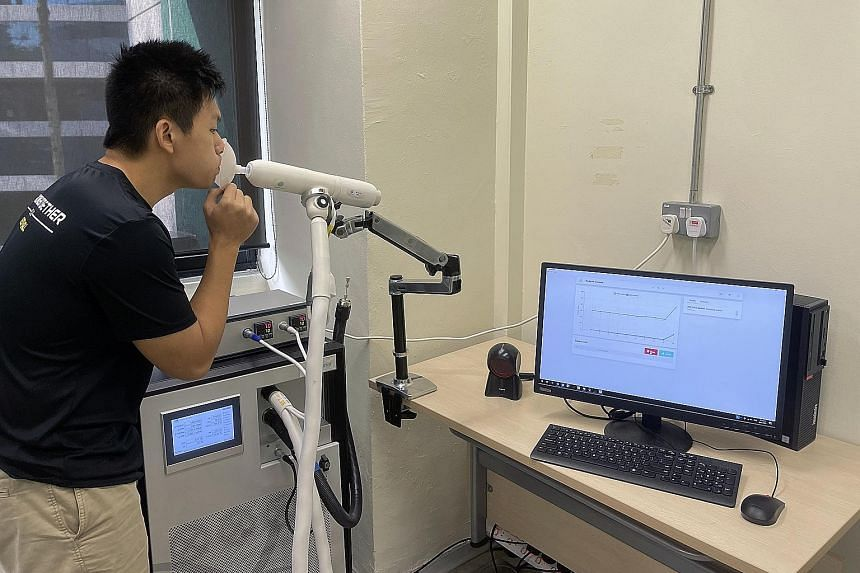 Mr Chan Tiong Ley, head of software and partnerships at Breathonix, demonstrating how the non-invasive breath test system is used. A person being tested for Covid-19 simply breathes out into a disposable mouthpiece connected to a breath sampler.