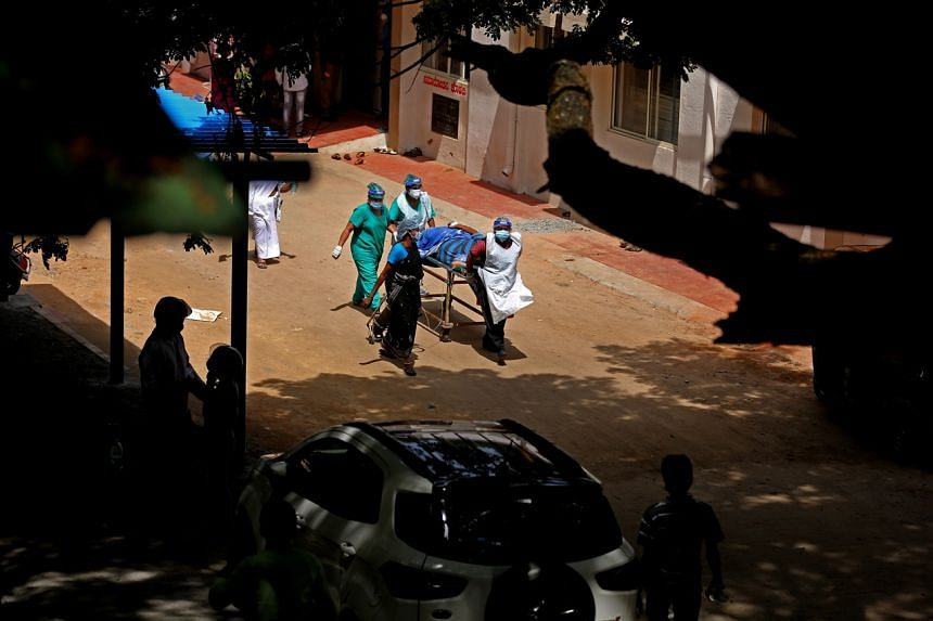 Health officials bring a suspected Covid-19 patient at KC General hospital in Bangalore, India, on May 24, 2021.