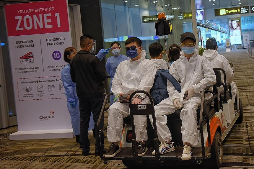 Outbound passengers wearing PPE while on their way to the departure gates in Changi Airport Terminal 3 on May 24, 2021.